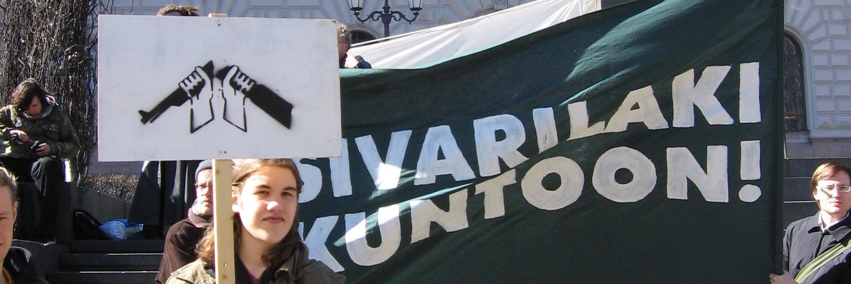 Mielenosoittaja kantaa plakaatia, jossa on kuvattuna katkaistu kivääri. Taustalla banderolli: Sivarilaki kuntoon.