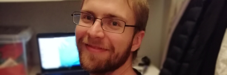 Aku Kervinen istuu katsoen hymyillen kameraan. Hänellä on sylissään näppäimistö, takana näkyy avoin tietokone ja kirjahylly.