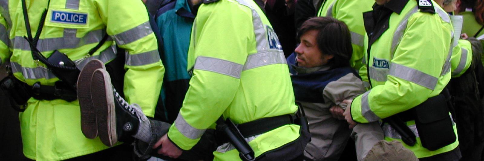 Poliisit kantavat mielenosoittaja pois Faslanen portilta.
