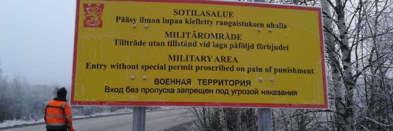 Harmaassa maisemassa kyltti: Sotilasalue. Siviileiltä pääsy kielletty.
