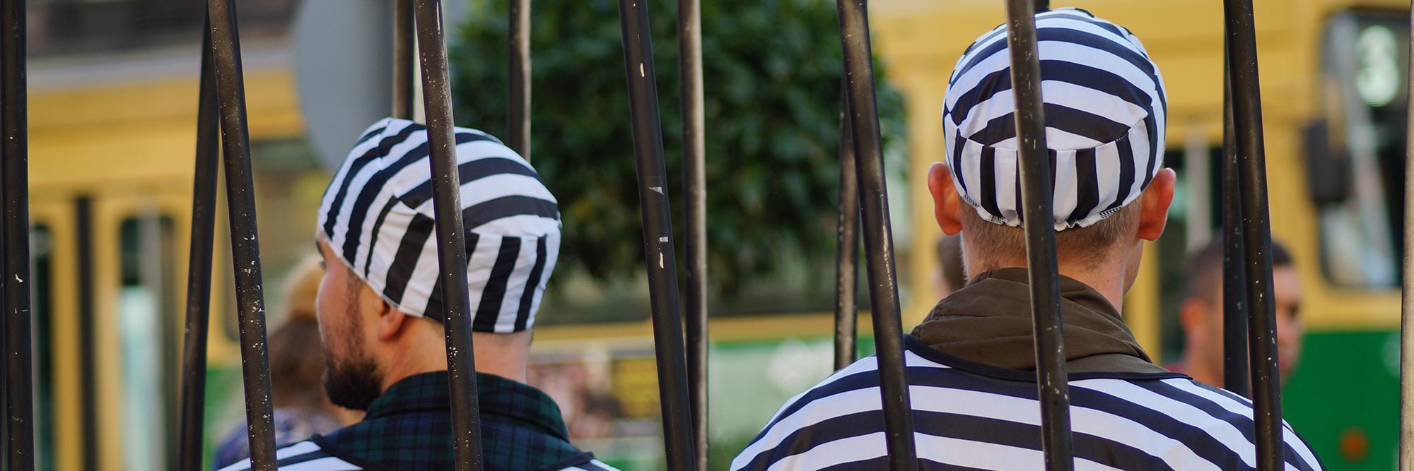 Kaksi vankipukuista miesoletettua kaltereiden takana