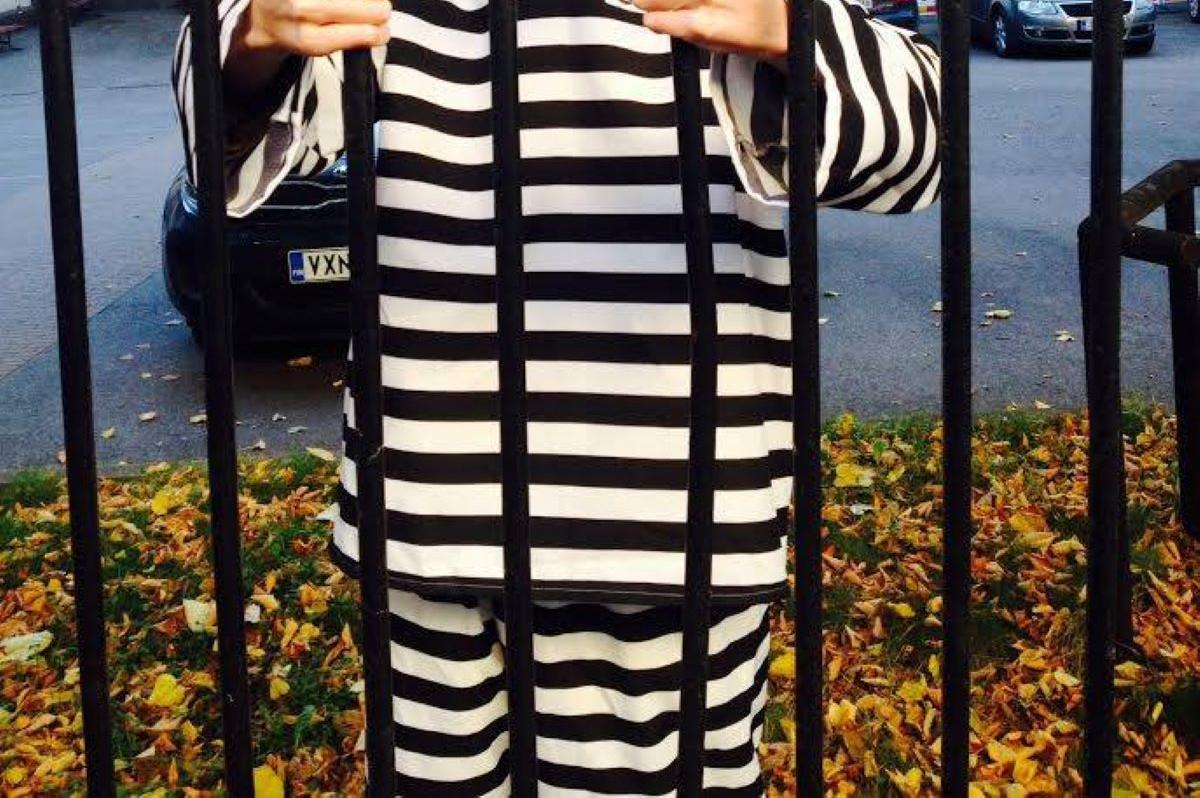 Valkomustaraidalliseen vanginasuun pukeutunut mielenosoittaja seisoo häkissä.