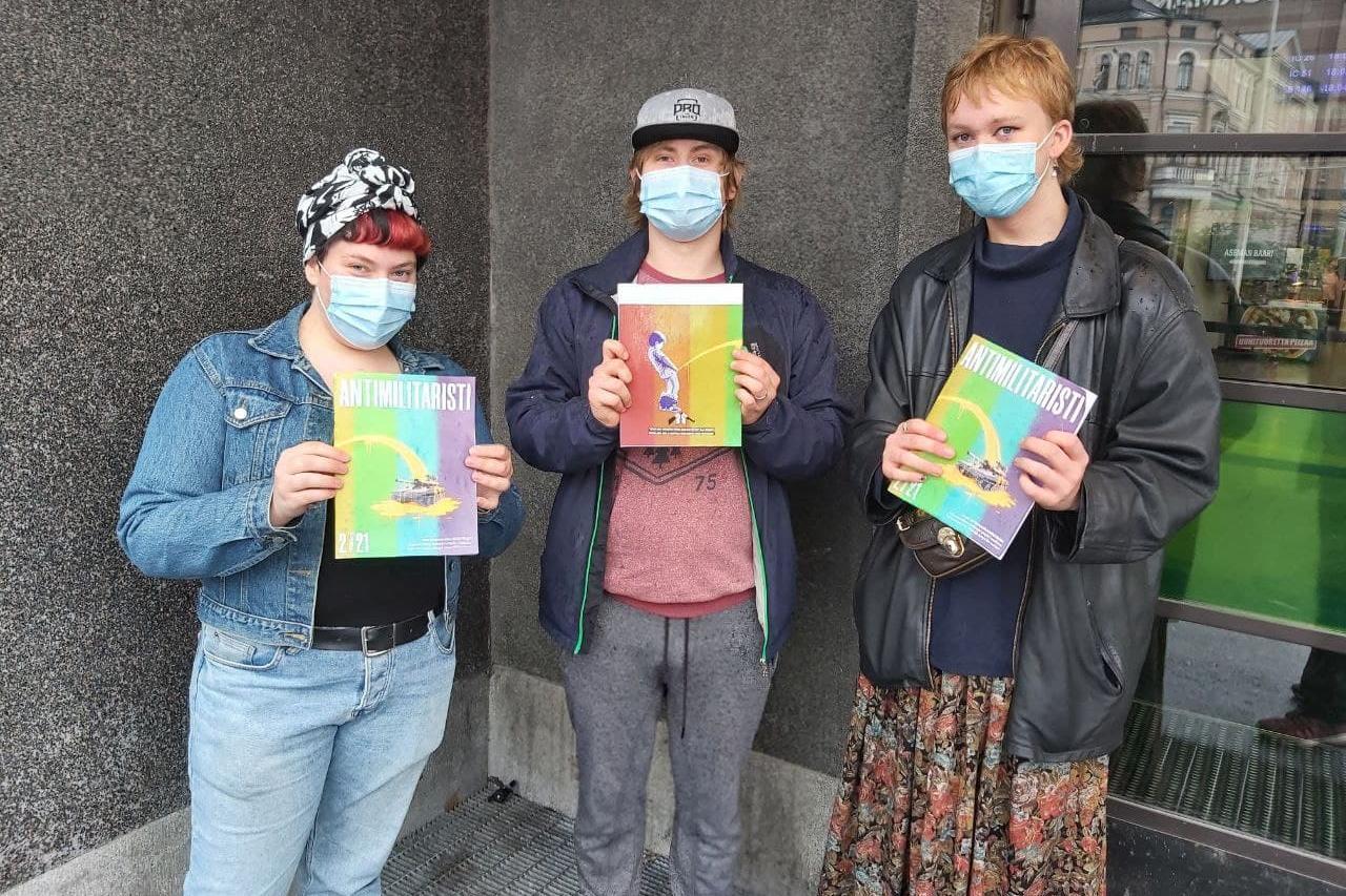 Kolme henkilöä seisoo kasvimaskit päässä ja Antimilitaristi-lehdet käsissään kiviseinää vasten.