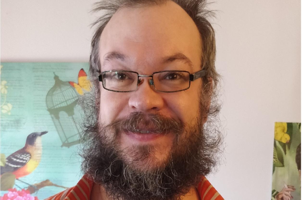 Värikkääseen kauluspaitaan sonnustautunut Jussi Koiranen hymyilee kameralle. Taustalla lintua ja tupakoivaa henkilöä esittävät maalaukset.