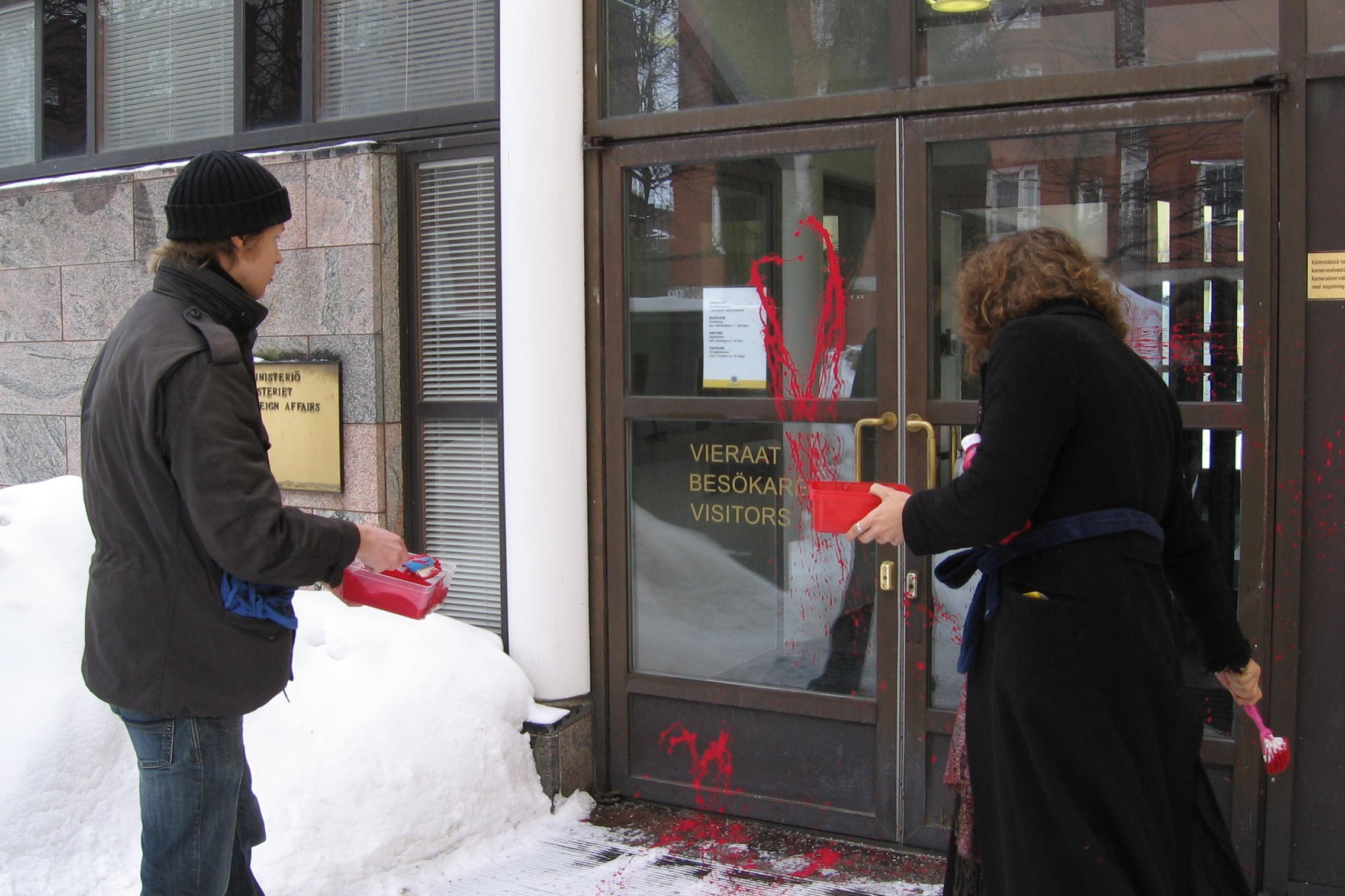 Ulkoasiainministeriö tahriutuu verenpunaiseen protestina NATO-lähentymistä vastaan.