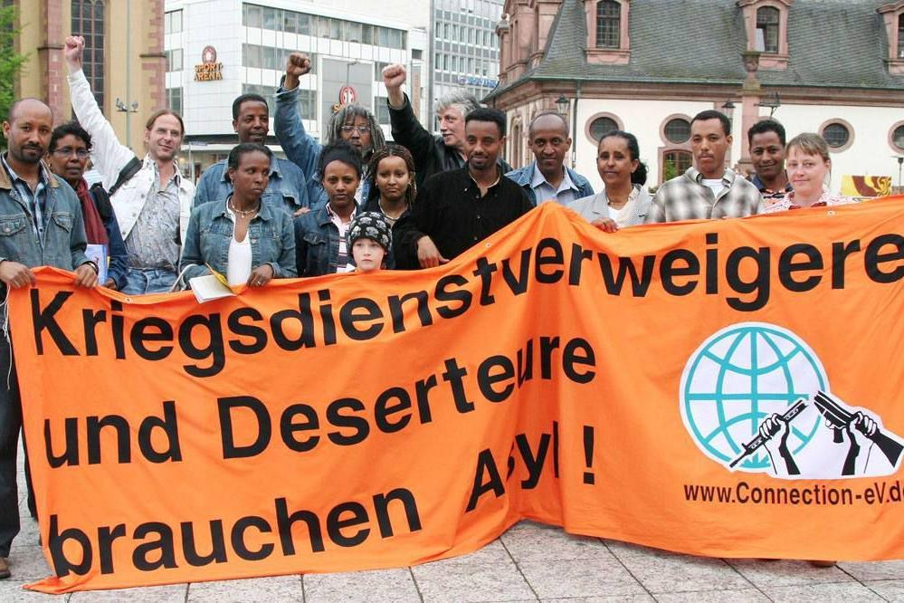 """Kuvassa: Mielenosoitus eritrealaisten turvapaikanhakijoiden puolesta Saksassa. Banderollissa lukee: """"Aseistakieltäytyjät tarvitsevat turvapaikan!"""""""