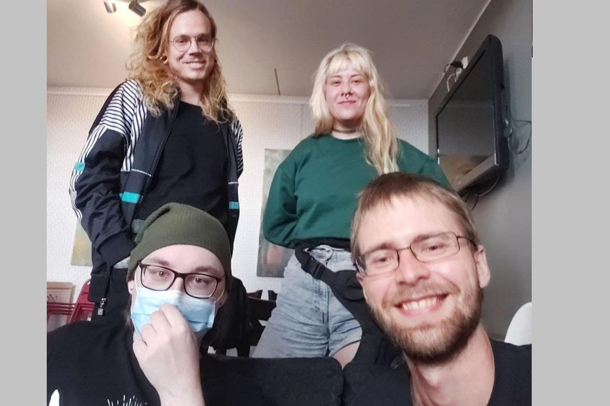 Neljä nuorta henkilöä katsoo kameraan hymyillen.