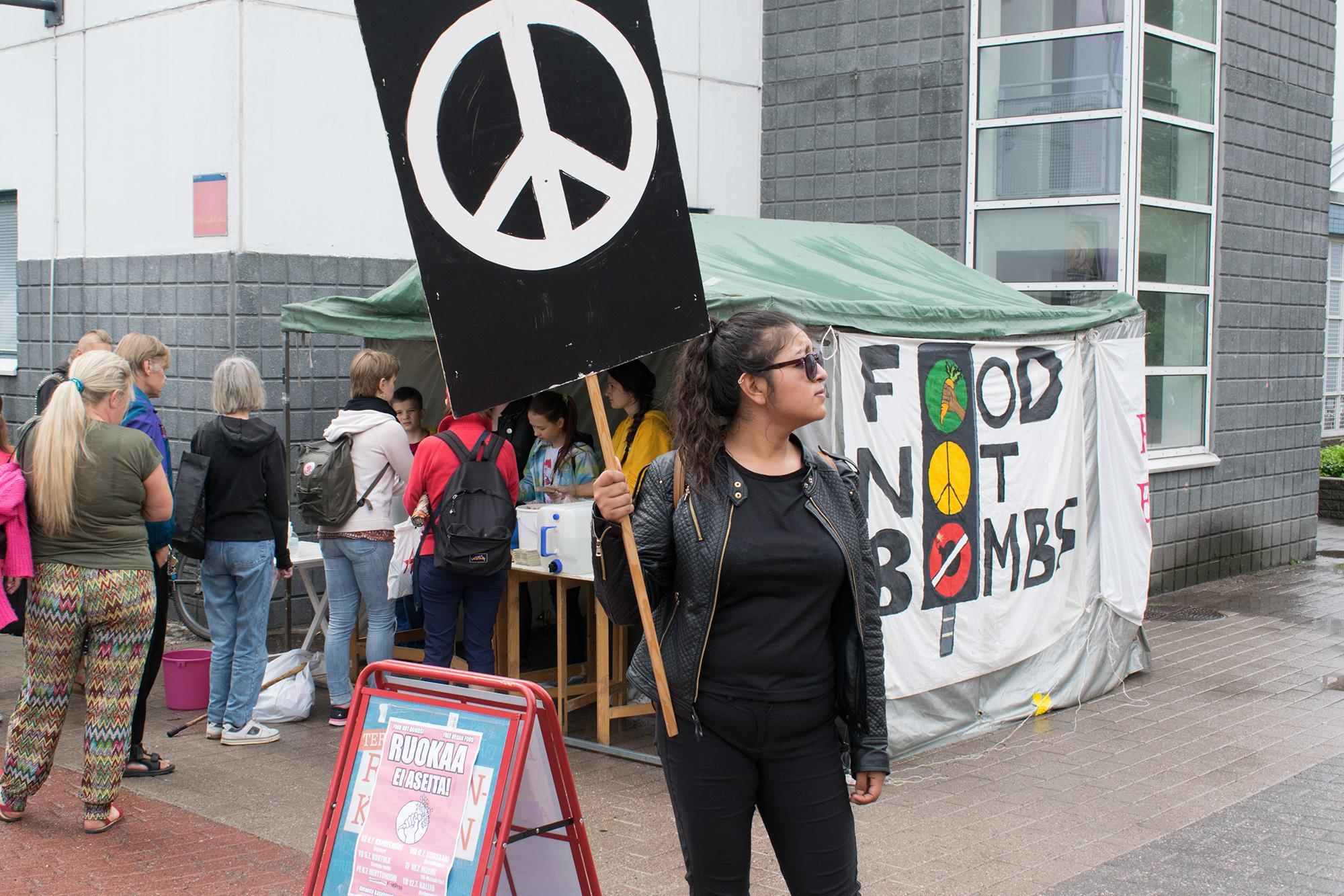 Mustiinpukeutunut ihminen seisoo pidellen kylttiä, jossa on suuri rauhanmerkki. Taustalla ihmiset jonottavat teltalle, jonka seinänä on Food Not Bombs -banderolli.