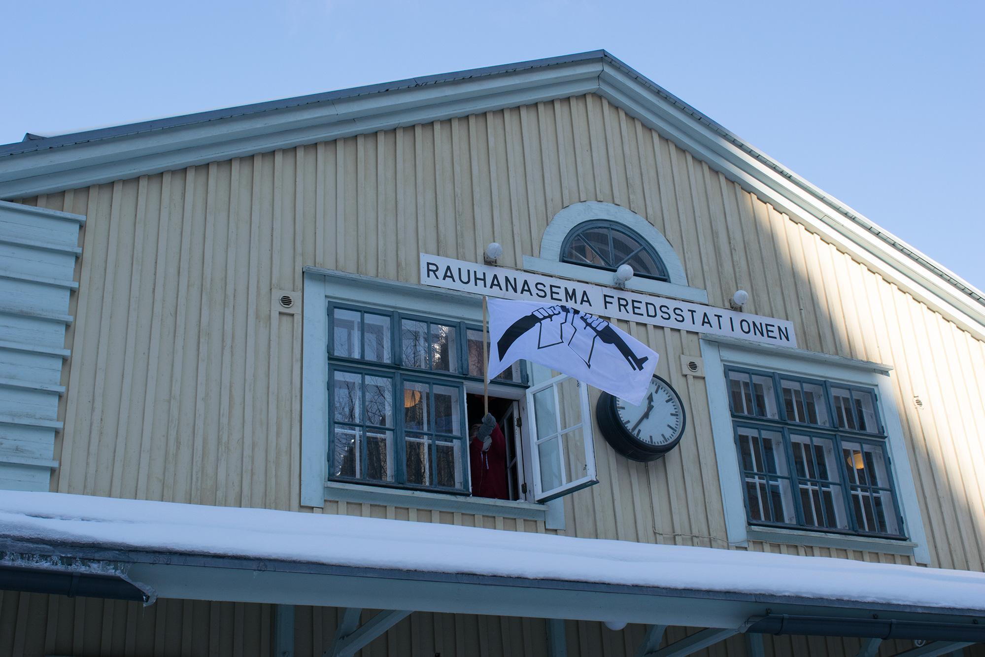 Ihminen heiluttaa AKL:n katkaistu kivääri -lippua symaattisen näköisen puurakennuksen ikkunasta. Rakennuksen seinässä on teksti: Rauhanasema - Fredsstationen.