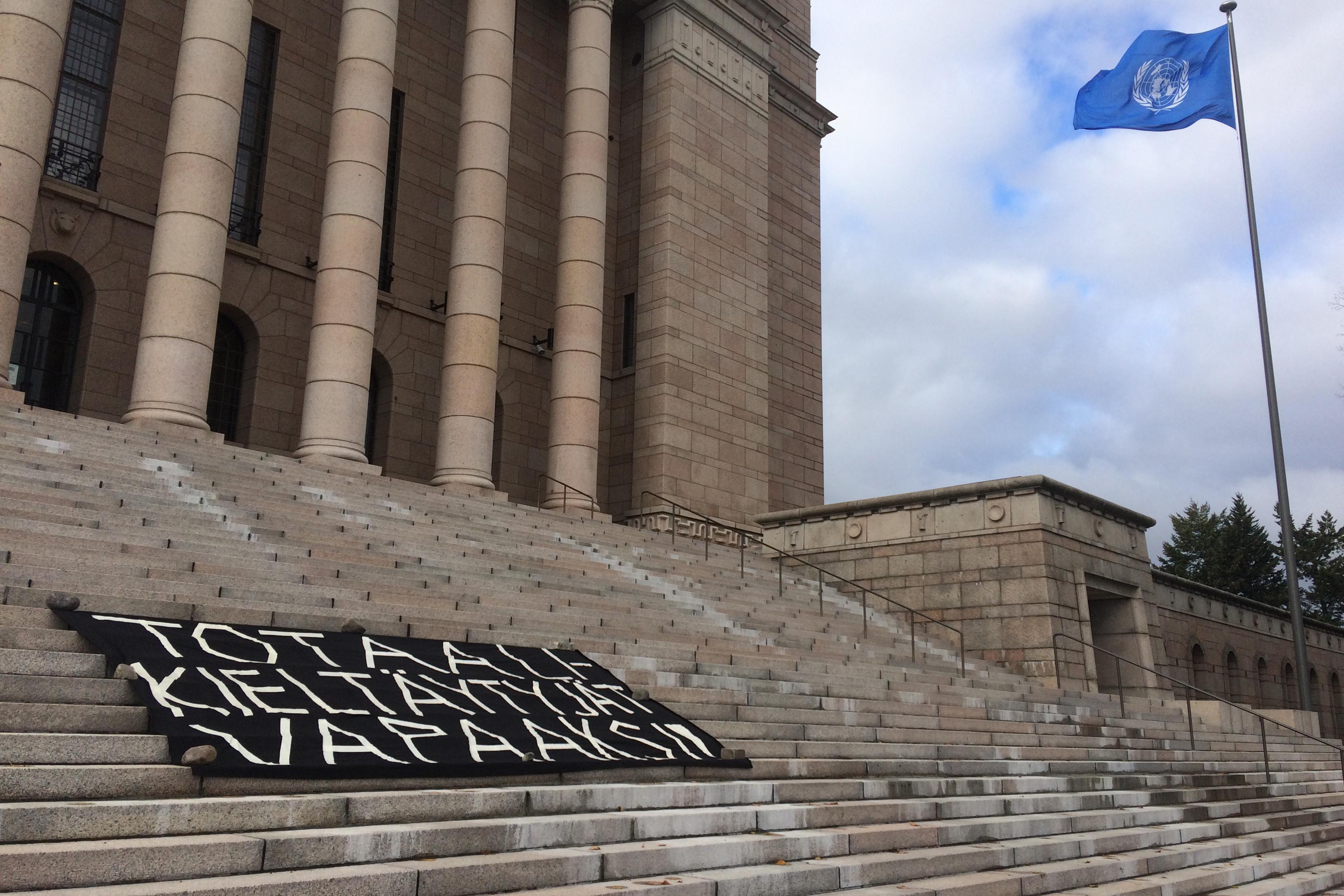 Totaalikieltäytyjät vapaaksi -banderolli eduskuntatalon portailla.
